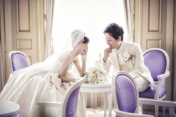 結婚式場にある大好きな薄紫色のイスをアクセントに満面の笑みで