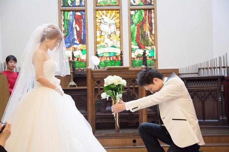 結婚式の人前式でゲストから集めた12本の白いバラの花束を差し出して跪いてプロポーズする新郎