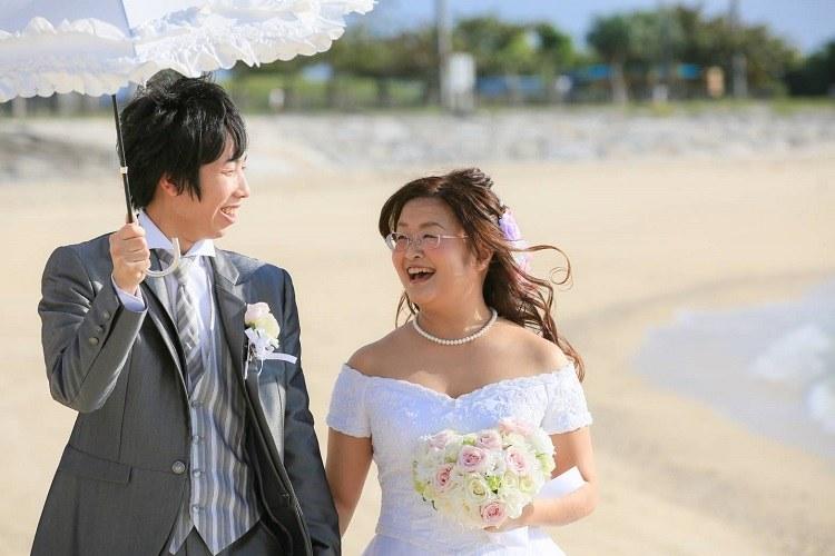 結婚式当日に沖縄のビーチにて海から届く気持ちいい風に満面の笑み