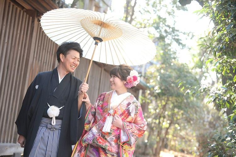 やわらかい日差しのなかで番傘を差して仲良く歩く見つめあいショットも結婚式の前撮りのオススメポーズ