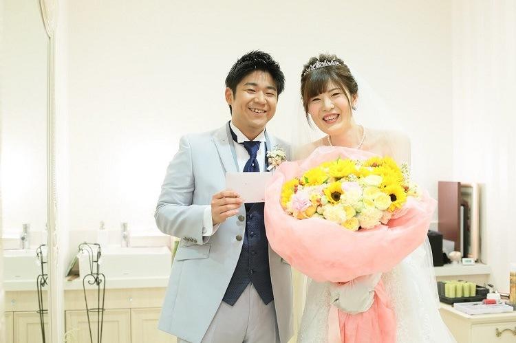 結婚式直前の控え室で花束と手紙をもらった新郎新婦並んで記念撮影